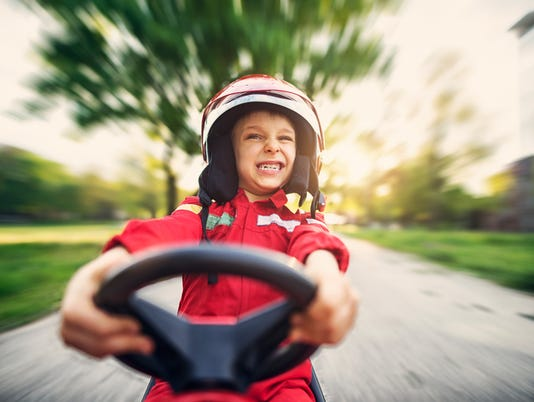 Portrait of little boy driving fast his toy car