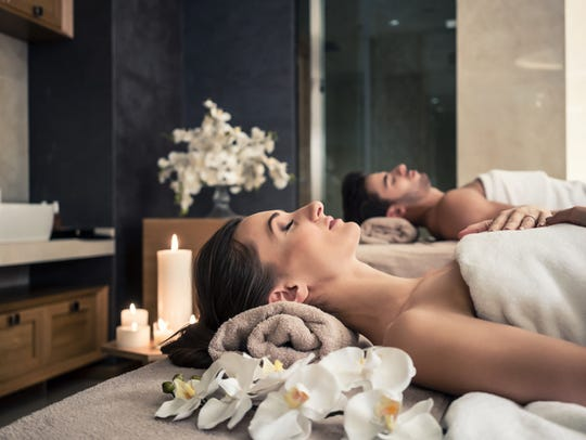 Young man and woman lying down on massage beds at Asian
