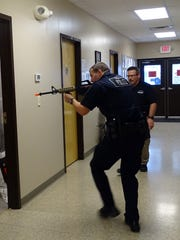 Chillicothe Police Officer Cody Moore checks a room during a 2017 active shooter training while Community Resource Officer Bud Lytle, who conducted the training, observes at the Camp Sherman Training Center.