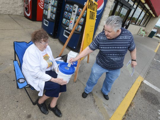 Barbara Mendelson, left accepts a donation for Christ's Table from Celena Crothers outside Riesbeck's Food Market in downtown Zanesville on Friday. The local food pantry is collecting donations to fund additional meals served during the summer.