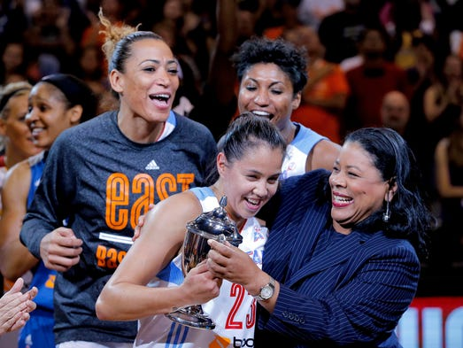East's Shoni Schimmel, of the Atlanta Dream, is presented the MVP trophy by WNBA President Laurel J. Richie, right, after the WNBA All-Star basketball game, Saturday, July 19, 2014, in Phoenix. The East won 125-124 in overtime. (AP Photo/Matt York)