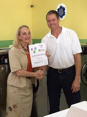 Cecelia De Filippis, director of philanthropy for St. Lucie Habitat for Humanity, and Tom Rhodes, co-owner of Sunshine Laundries, with the thank you sign from the washer indicating how much was raised.