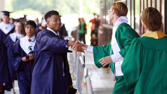 Comeaux High School graduate John Jones, left, greets soon-to-be Lafayette High graduate Jacob LeMeunier at 2015 ceremonies.
