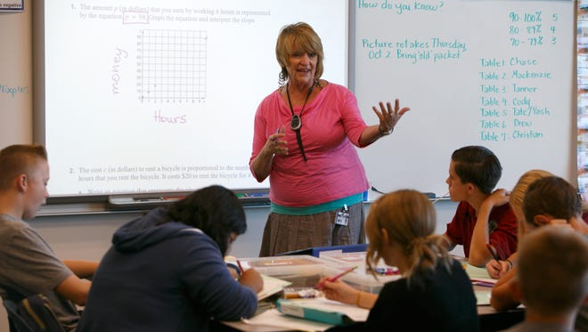 Dixie MIddle School math teacher Kris Cunningham goes over a graphing problem with an 8th grade honors math class Tuesday, Sep. 30, 2014.