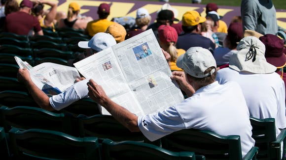 Sun Devil fans read the paper during a lil in game
