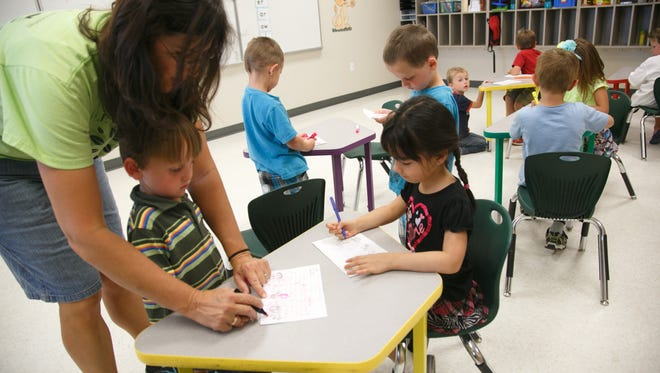 "Kindergarten teacher MaryAnn Johnson helps preschool aged students learn about the letter ""C"" during a summer school class at Valley Academy in Hurricane in 2014."