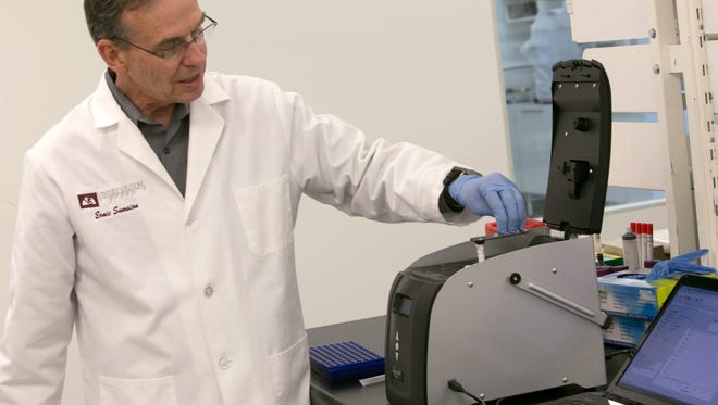 DxNA chief operating officer Ernie Sumsion load a test cartridge into one of his company's GeneSTAT machines in DxNA's St. George lab Wednesday, June 5, 2013.