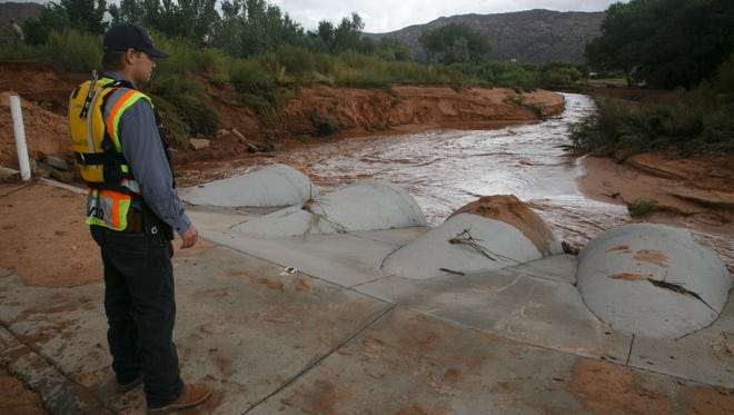 Hildale/Colorado City Fire Department firefighter and Search and Rescue team member Chester Barlow keeps an eye on the waters of Short Creek Tuesday, Sep. 15, 2015 as efforts continue to find people still missing after flash floods ripped through the area.