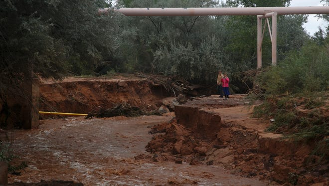 Rescuers search the banks of Short Creek Tuesday, Sept. 15, 2015 looking for people still missing after flash floods ripped through the twin towns of Hildale and Colorado City.