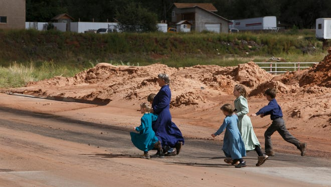 Residents of the town towns of Hildale and Colorado City look on as efforts to remove debris on Richard Street in Colorado City continues Tuesday, Sep. 15, 2015. Search and rescue personnel are still looking for five people missing after flash floods swept through the area on Monday.