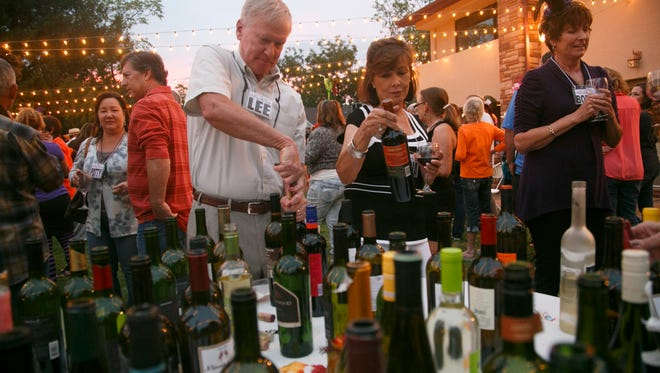 St. George Wine Club members sample the wines available at the club's October get-together at the DiFiore Center for the Arts Sunday, Oct. 25, 2015 in St. George.