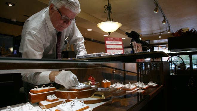 Tom McArthur works on setting up the jewelry displays at McArthur Jewelers Monday, Oct. 13, 2014.