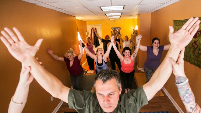 Greg Buehrle, of Hanover, and others transition into a Crescent Moon pose at the House of Yoga Tuesday, April 12, 2016. House of Yoga will be relocating to the corner of 19 W. Market St. Amanda J. Cain photo