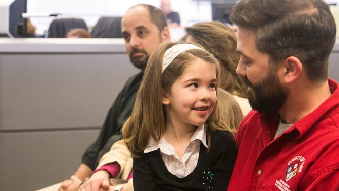 Mobile Data Computer Administrator Jonathan Grim, of Red Lion, shares a moment with his daughter Cassandra, 6, after receiving the Supervisor of the Year award, during the National Safety Telecommunicators Week annual ceremony at the York County 911 Center Friday, April 15, 2016. Amanda J. Cain photo