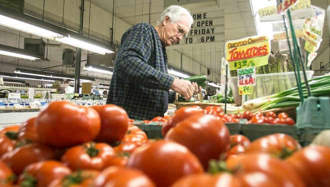 Harl Hughes, of Glenville, shops for Cucumbers at  the Brogue Hydroponics stand Friday, April 29, 2016, at New Eastern Market Co. Amanda J. Cain photo
