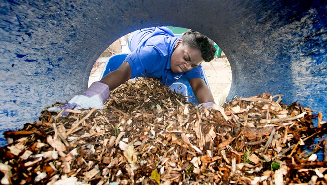 Crispus Attacks Youthbuild Charter student Emonie Pulley, 14, reaches up a shute to pull down mulch for the courtyard section of the Royal Square Community Garden Wednesday, May 25, 2016. The Crispus Attacks HYPE Program will be volunteering for the next two weeks to continue beautifying Royal Square Garden, which is located behind DiDi and Smiling Johns at 119 South Duke Street, just off the South Howard Avenue alleyway.Amanda J. Cain photo