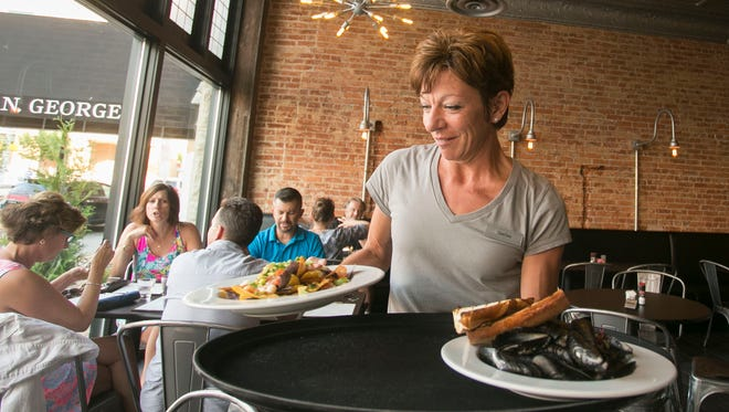 Rockfish Public House server DeeDee Brody delivers a plate of seafood nachos and a pound of mussels during her shift Friday, Aug. 12, 2016. The restaurant, which opened its doors Thursday, will officially open Tuesday. Amanda J. Cain photo