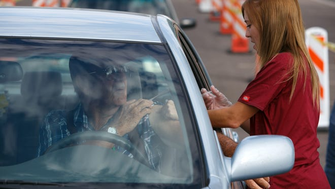 """Southwest Utah Public Health Department nurse Shannon Wood administers a flu shot during a vaccination """"Flu Shoot-Out"""" in the parking lot of the Red Cliffs Mall. Drivers lined up in the parking lot all morning to quickly and easily get their flu shots without ever having to leave their cars."""