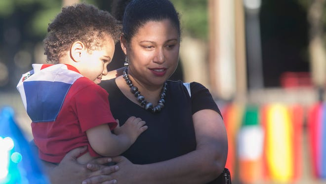 Ruth Tineo holds her son Joshua, 3, as they socialize during the Resource Fair at Welcoming week Saturday, Sept. 24, 2016, at Foundry Park. Amanda J. Cain photo