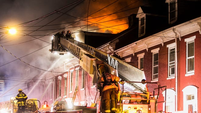 Firefighters respond to house fires on the 100 block of East Maple Street on Saturday, Oct. 29, 2016, in York City. The York chapter of the Red Cross helped 77 victims of disaster in October, most of them displaced by fires. Amanda J. Cain photo