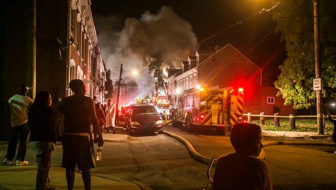 Bystanders watch as firefighters respond to house fires on the 100 block of East Maple Street Saturday, Oct. 29, 2016, in York City. Amanda J. Cain photo
