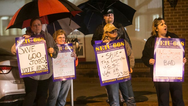 SEIU 668 members hold up signs outside of Senator Scott Wagner's office, as cars go by on N. George St. Wednesday, Nov. 30, 2016, in York City. Both the SEIU and York Progressives groups protested as a result to Senator Scott Wagner's decision not to vote on House Bill 2375. Amanda J. Cain photo