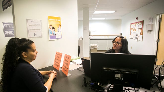 Certified Application Counselor Arlene Feliciano, of York City, talks with Medical Receptionist and co-worker Abigail Williams, left, of Mount Wolf during their shift Tuesday, Dec. 6, 2016, at the Family First Health- George Street Center, in York City. As a Certified Application Counselor, Feliciano helps guide people through open enrollment. Amanda J. Cain photo