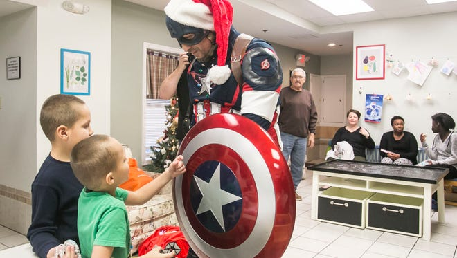 Mosiah, 6, and Moses Autry, 8, left, talk with Captain America, played by Jason Johnson, right, of Elizabethtown, during the Central PA Avengers gift-giving event at LifePath Ministries Women and Children's Shelter Saturday, Dec. 10, 2016, in York City. The Central PA Avengers are group of costume enthusiasts that have turned their love of costuming into a way to give back to their community. Amanda J. Cain photo