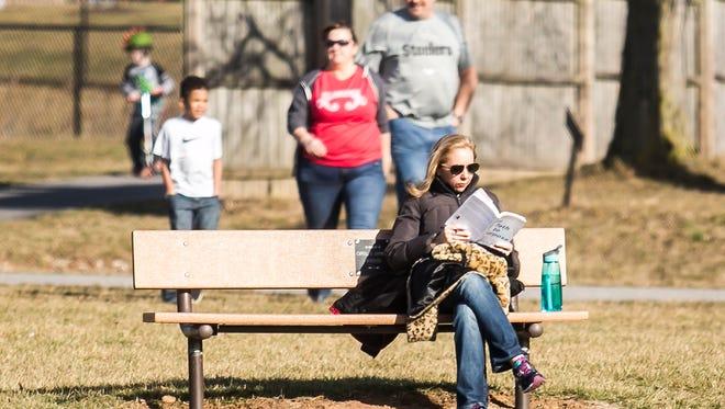 Christina VanVorst, of West York, reads a book while her children play on a beautiful afternoon at Cousler Park Saturday, Feb. 18, 2017, in Manchester Township. Amanda J. Cain photo