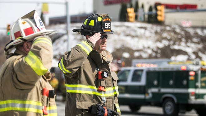 From left, Loganville 63 Volunteer Asst. Chief Dale Dubbs and York City Volunteer firefighter Fred Shilke salute, as Lt. Dennis H. DeVoe's Funeral Procession, comes down East Forrest Ave. Saturday, March 18, 2017, in Shrewsbury. Amanda J. Cain photo