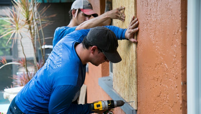 Agustin Ponce, right, and Mike Park with Beattie Development and Builder's Care put up plywood on the home of Shirley St. Onge on Wednesday in North Fort Myers.
