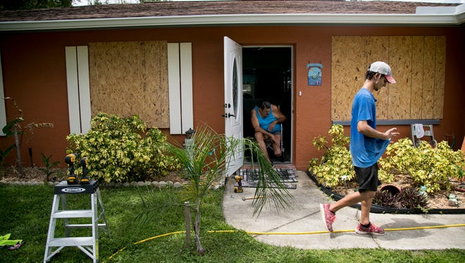 Norman St. Onge looks out the door of his North Fort Myers home as a crew from Beattie Development boads up his windows on Wednesday ahead of Hurricane Irma. Builder's Care coordinated the effort.
