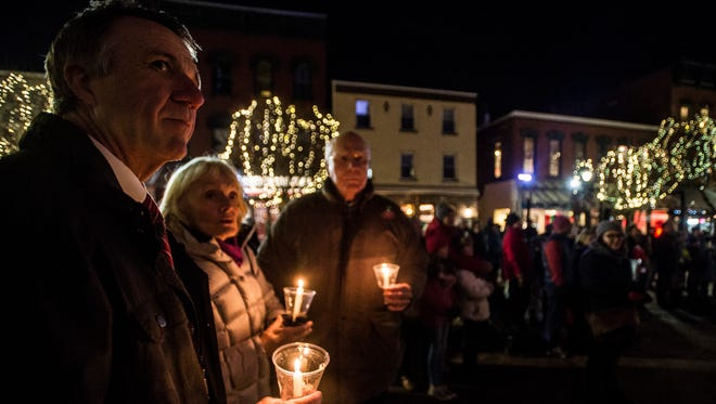 From left, then Governor-elect Phil Scott, Marcelle Leahy and husband Sen. Patrick Leahy, D-VT, listen to COTS Executive Director Rita Markley read names of people who have struggled with homelessness during a vigil in December 2016 outside of Burlington City Hall.