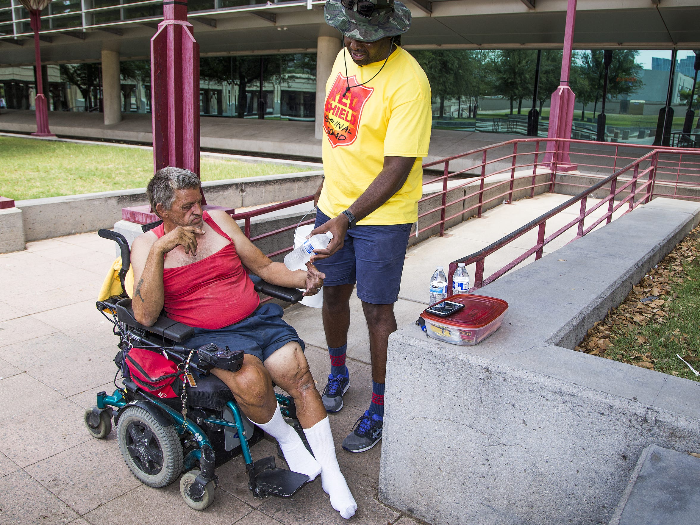 Jowan Thornton, right, of the Red Shield Survival Squad of the Salvation Army, hands water to Terry Reck, 59, near a Phoenix park last June.