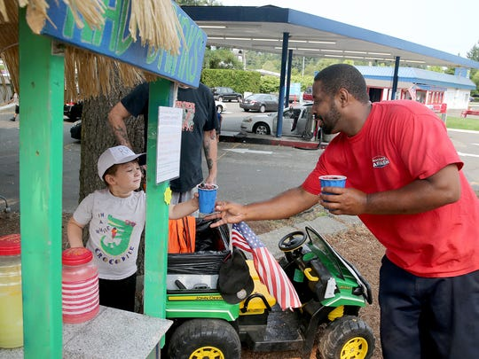 Four-year-old Rylee Allowishes Delaney is CEO and president of RAD Drinks, serves a drink for a customer  Shur-Kleen  Car Wash worker Tyrone Harris in West Bremerton.