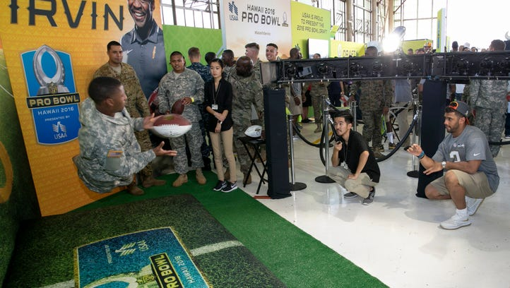 Seattle Seahawks quarterback Russell Wilson (3) tosses a football to a soldier at the NFL Pro Bowl football draft at Wheeler Army Airfield, Wednesday, Jan. 27, 2016, in Wahiawa, Hawaii.