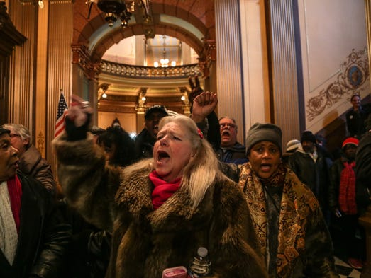 Flint resident Gladyes Williamson (center) shouts with
