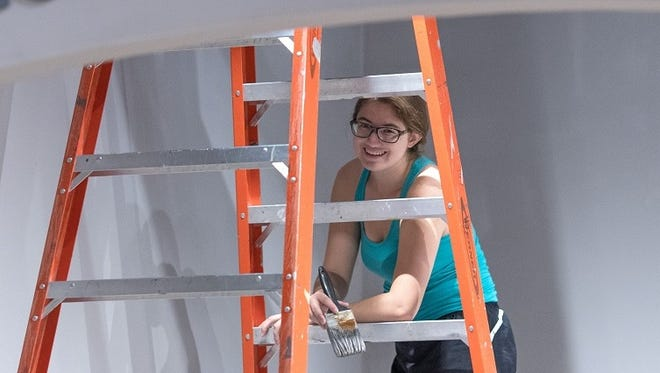 """Meghan Wagner, an arts management student at UW-Stevens Point, who is curating a special exhibit for the """"2017 Federal Duck Stamp Contest,"""" prepares the university's Edna Carlsten Art Gallery for the show."""