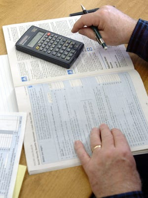 A man fills out his taxes in this file photo.