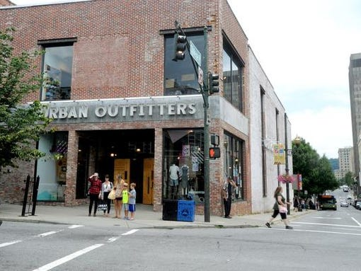 Pedestrians walk past the Urban Outfitters at College