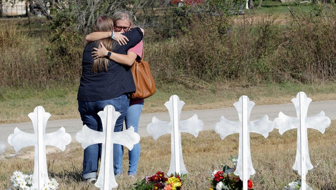 Two women hug at a makeshift memorial for the First Baptist Church shooting victims  in Sutherland Springs, TX, Nov. 7, 2017.  A man opened fire inside the church in the small South Texas community on Sunday, killing more than two dozen and injuring others.