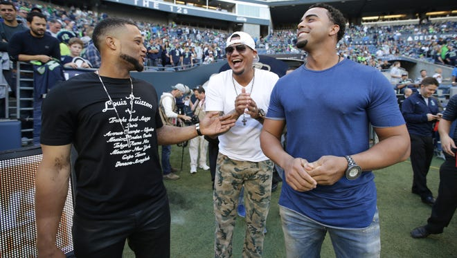 Seattle Mariners baseball players Robinson Cano, Felix Hernandez, and Nelson Cruz visit the Seattle Seahawks sideline before an NFL football game between the Seahawks and the Detroit Lions, in Seattle. All-Star second baseman Robinson Cano is supremely fashion-conscious, and he talks with joy about the collection in his massive closet.(AP Photo/Scott Eklund, File)