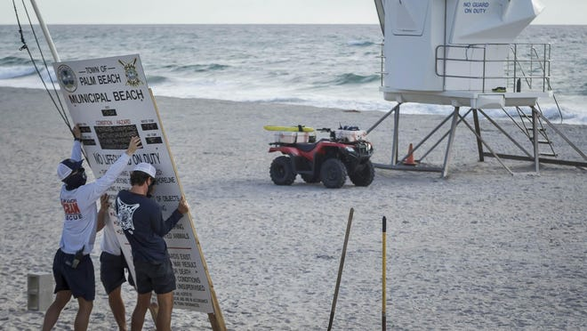 Palm Beach Ocean Rescue personnel take down the weather conditions signage in preparation for Hurricane Isaias in Palm Beach on Saturday. Forecasters are indicating there may be hurricane force winds in the county on Sunday.