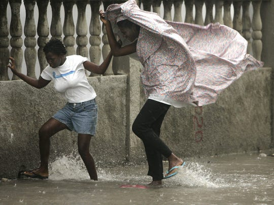 Two women look for shelter during light rain and strong wind from Hurricane Dean as it moves along Haiti's southern coast in Les Cayes, about 92 miles from Port-au-Prince on Aug. 19, 2007.