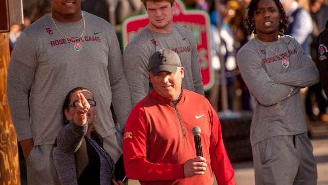 Southern California coach Clay Helton, center front, and players Zach Banner, Sam Darnold and Adoree Jackson, from left, stand for photos after a short welcome ceremony at Disney California Adventure in Anaheim.