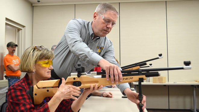 John White, co-owner of Two-Gun Tactical in Flowood, helps adjust a gun mount for Sheila Burnham of Madison during a marksmanship clinic organized by Methodist Rehabilitation Center in Jackson.