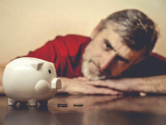 Senior man looking at piggy bank