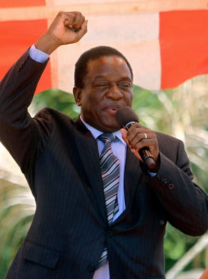 In this Wednesday Feb, 10, 2016 file photo, then-Zimbabwean vice President Emmerson Mnangagwa greets party supporters at the ZANU-PF headquarters in Harare.