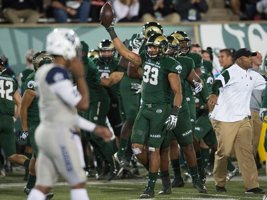 CSU linebacker Kevin Davis holds the ball high after a turnover during a game against Utah State at Hughes Stadium Saturday, October 8, 2016.