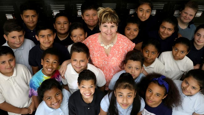 """Jacqueline Waldron is surrounded by her third grade class at Harms Elementary in Detroit on Tuesday, June 12, 2018. Waldron was named the Goodfellow Teacher of the Year. Two of her students wrote letters of nomination in 50 words or less on the topic """"Why is your teacher so special?"""""""